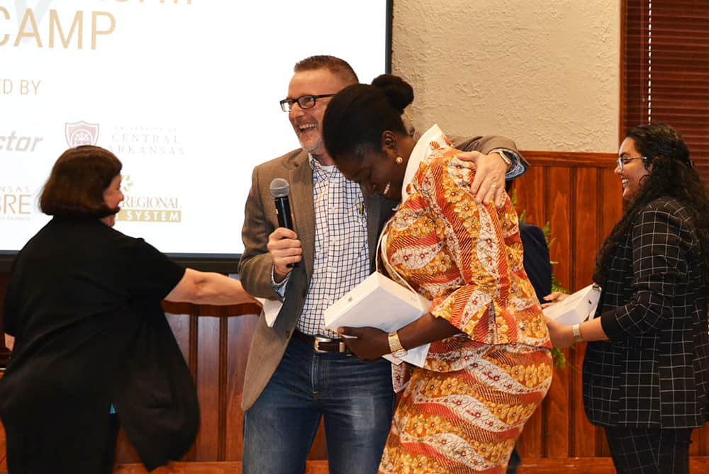 Jeff Standridge, center, embraces a tearful Selom Ayawovi Ametepe in celebration after the announcement that PAKI Solutions, Ametepe's team, had won the Boot Camp competition. Nancy Gray, left, shakes the hand of another team member.
