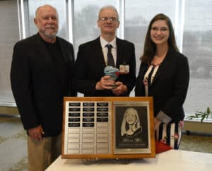 Michael Arnold, (center) a Nutrition Services employee in the Cafeteria, was presented with the Helen May Compassionate Care Award. He is pictured with Jim May and Katelyn Johnson, Helen May's husband and daughter.