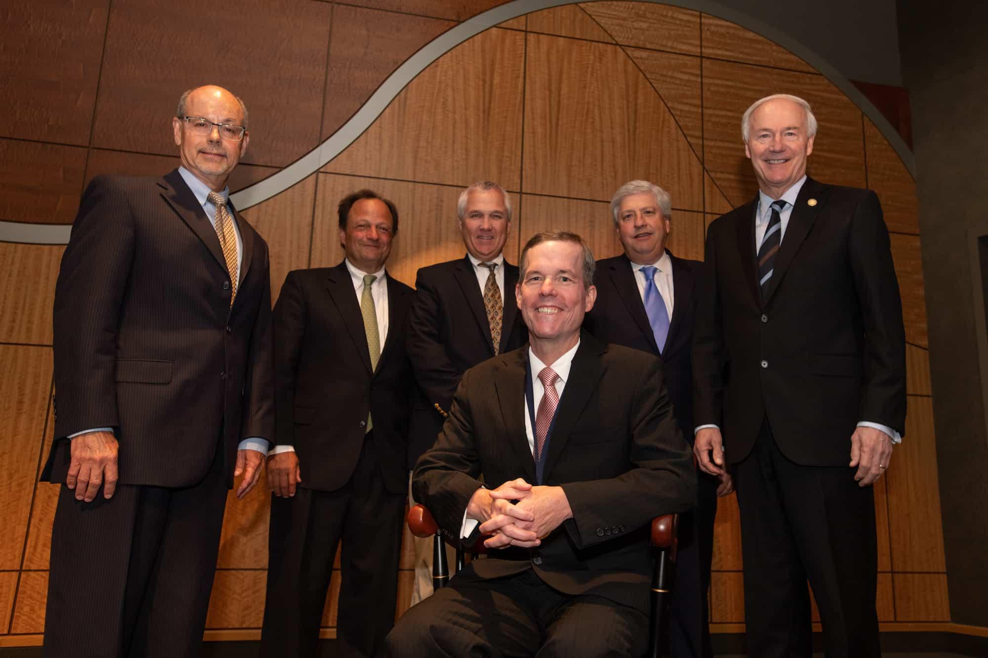 Patterson sits in his chair at the investiture ceremony. Behind him are (from left to right): Donald Bobbitt, Ph.D., Michael E. Mendelsohn, M.D., Steve Carpenter, M.D., John Goodson, and Gov. Asa Hutchinson.