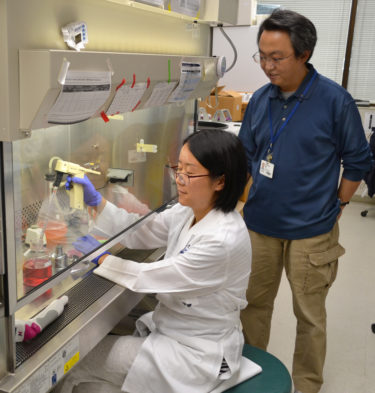 Mu and Liu in lab using fume hood