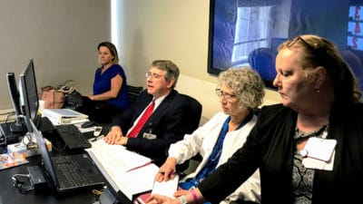On the UAMS main campus in Little Rock, T. Glenn Pait, M.D., second from left, consults with a spine patient at one the UAMS Regional Campus locations
