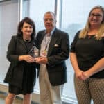 Larry Lichty (center) is this year's Volunteer of the Year, honored for his work with the Connections Team serving international patients. Congratulating him on his award are Jane Corley, director of international patient services (left) and Chrissy Adams, international finance manager.