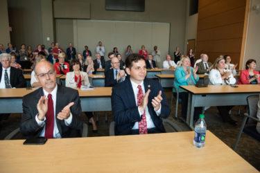 University of Arkansas System President Donald R. Bobbitt, Ph.D., front left, and Jimmy Harris, front right, Little Rock field representative for U.S., Sen. John Boozman, applaud the announcement.
