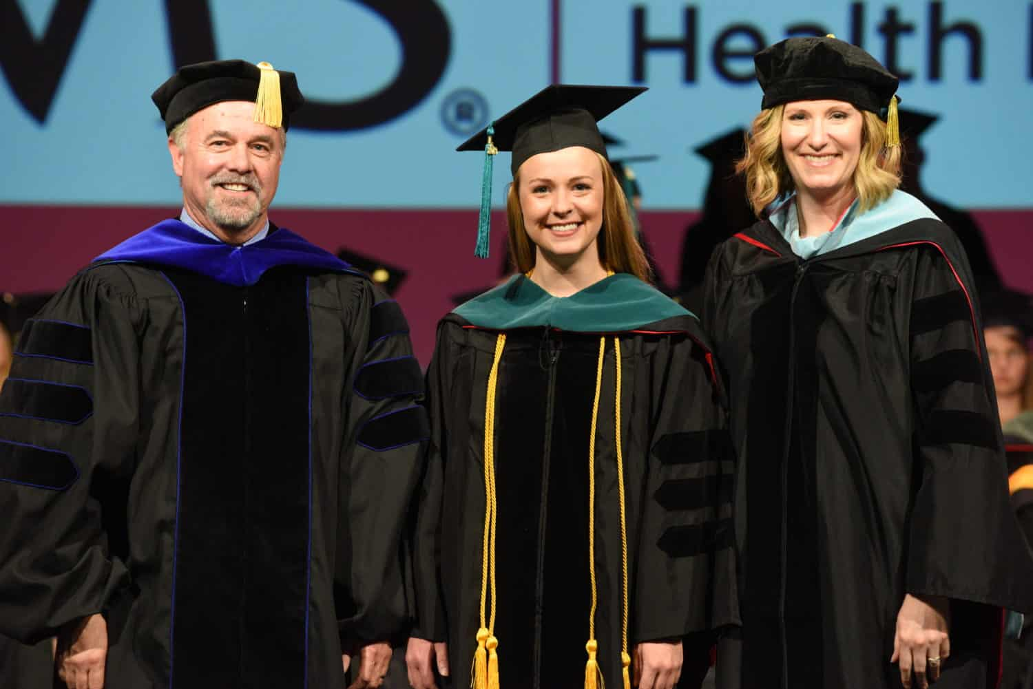 Kayla Copeland (center) is all smiles after receiving her academic hood from John Jefferson, Ph.D., chair of the Department of Physical Therapy, and Angel Holland, Ed.D., assistant professor. Copeland said she got a little teary when she saw her name -- Dr. Kayla Copeland -- on a sign.