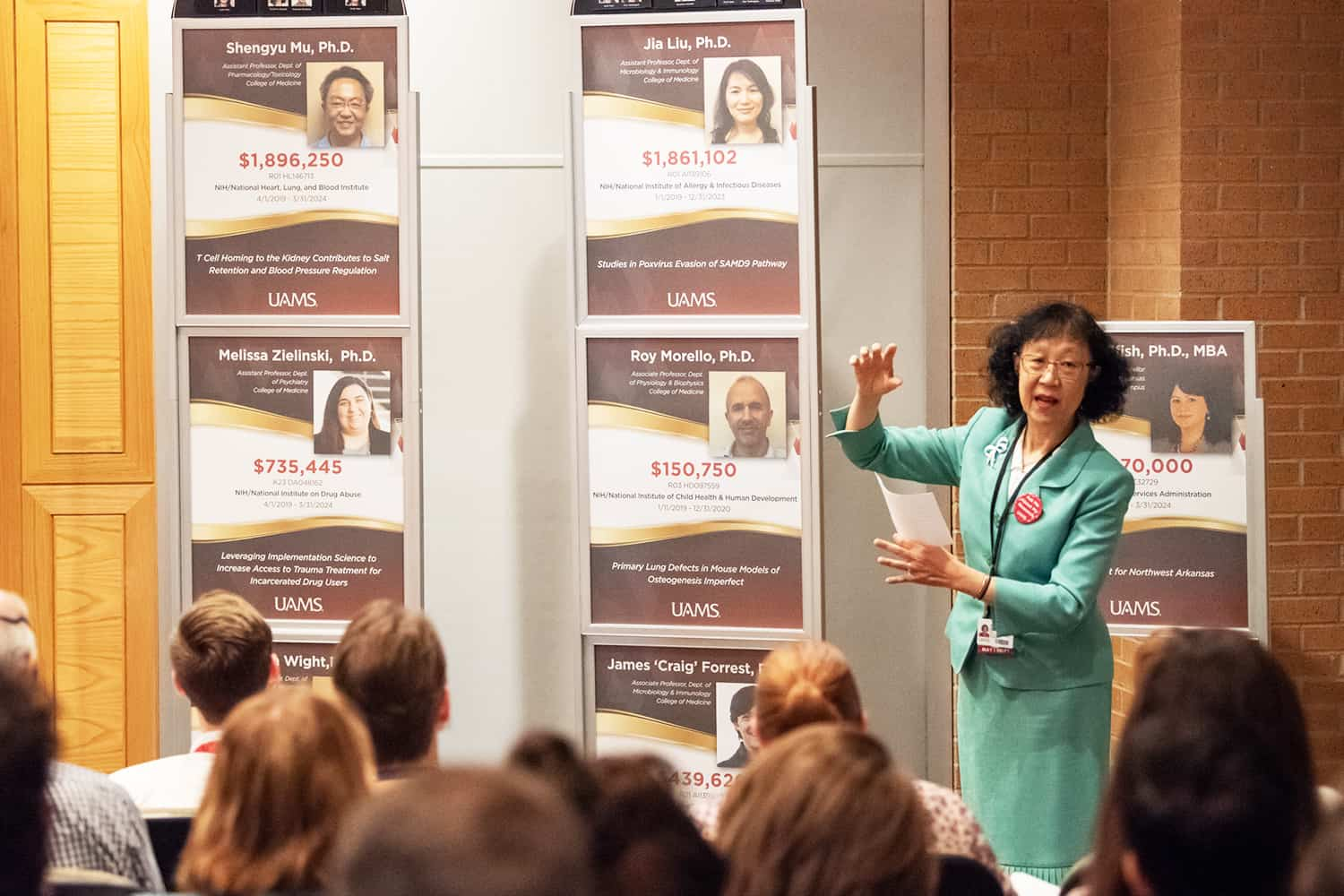 Shuk-Mei Ho, Ph.D., UAMS vice chancellor for research, presents two new displays celebrating recent grants to UAMS researchers.
