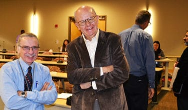 Peter Crooks, Ph.D., D.Sc., left, and Cesar Compadre, Ph.D., stop to talk during a break at the colloquium.