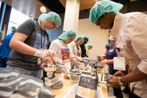 Members of Team UAMS weigh and seal the completed meal kits. More than 170 employees volunteered to help at the Feed the Funnel event July 9. <i>Photo credit, Bryan Clifton</i>