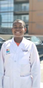 A Junior STEM Academy student shows off his white coat.