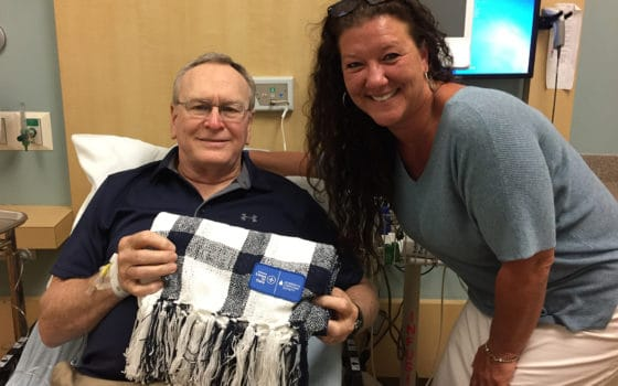 Myeloma patient John Tyler of Conway accepts a blanket from Shane Haas, communications manager of Subaru of Little Rock