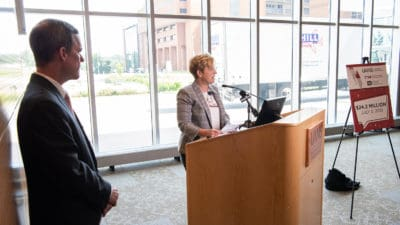 UAMS Chancellor Cam Patterson, left, listens to Laura James, M.D., director of the UAMS Translational Research Institute after both of them announced $24.2 million in new funding for the institute.