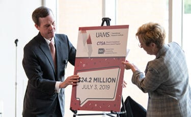 Patterson, left, and James finish unveiling a poster announcing the grant award.