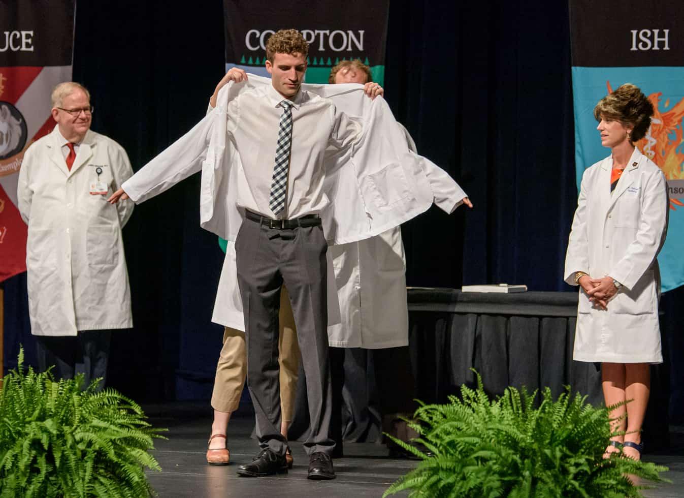Student putting on white coat