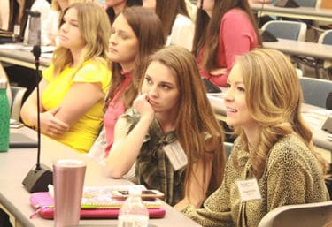 Claudio Raffo, right, a former Miss Arkansas 2018, watches as student models take the stage to explain dress code do's and don'ts to the first year students.