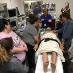 Pam deGravelles (center) gives nursing students an introduction to the operating room simulation suite and high-fidelity manikin.