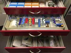 A crash cart filled with an array of medications, represented by distilled water, organized as they would be in the operating room.