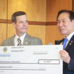 UAMS Chancellor Cam Patterson receives a donation supporting Regional Programs from Jung-Yul Choi, president of the Lions Club International Foundation.
