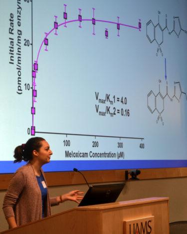 Femal student at podium giving oral presentation