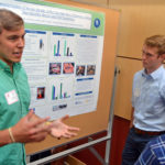Two male students presenting research at poster