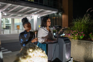 SNMA President Tia'Asia James and member Paige Jones lead attendees in lighting candles and observing a moment of silence.