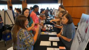 Nancy Gray, Ph.D., (right, front) president of BioVentures LLC, helped visitors to her booth understand the services BioVentures provides to UAMS researchers.