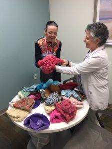 Linda House, administrative coordinator, and Margaret Syrgley, social worker with the UAMS Myeloma Center, sort the hats Ferren crafted and donated to the UAMS Winthrop P. Rockefeller Cancer Institute.