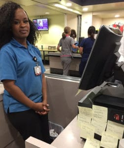 Brittany Missouri, a cashier in the main UAMS cafeteria, works amid encouraging notes given to her during Kindness Week.