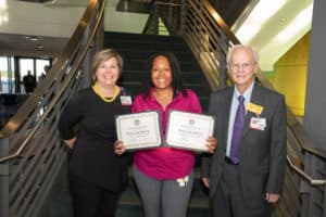 Scholarship recipient Shawanda McCoy, (center) gets a photo with Alicia Baird, chair of the Department of Ophthalmic Technologies, and John Shock, M.D., founder of the UAMS Jones Eye Institute.