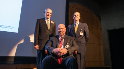 J.D. Day, M.D. (seated) wears his commemorative medallion from the investiture alongside UAMS College of Medicine Dean Christopher T. Westfall, M.D., FACS and UAMS Chancellor Cam Patterson, M.D., MBA.