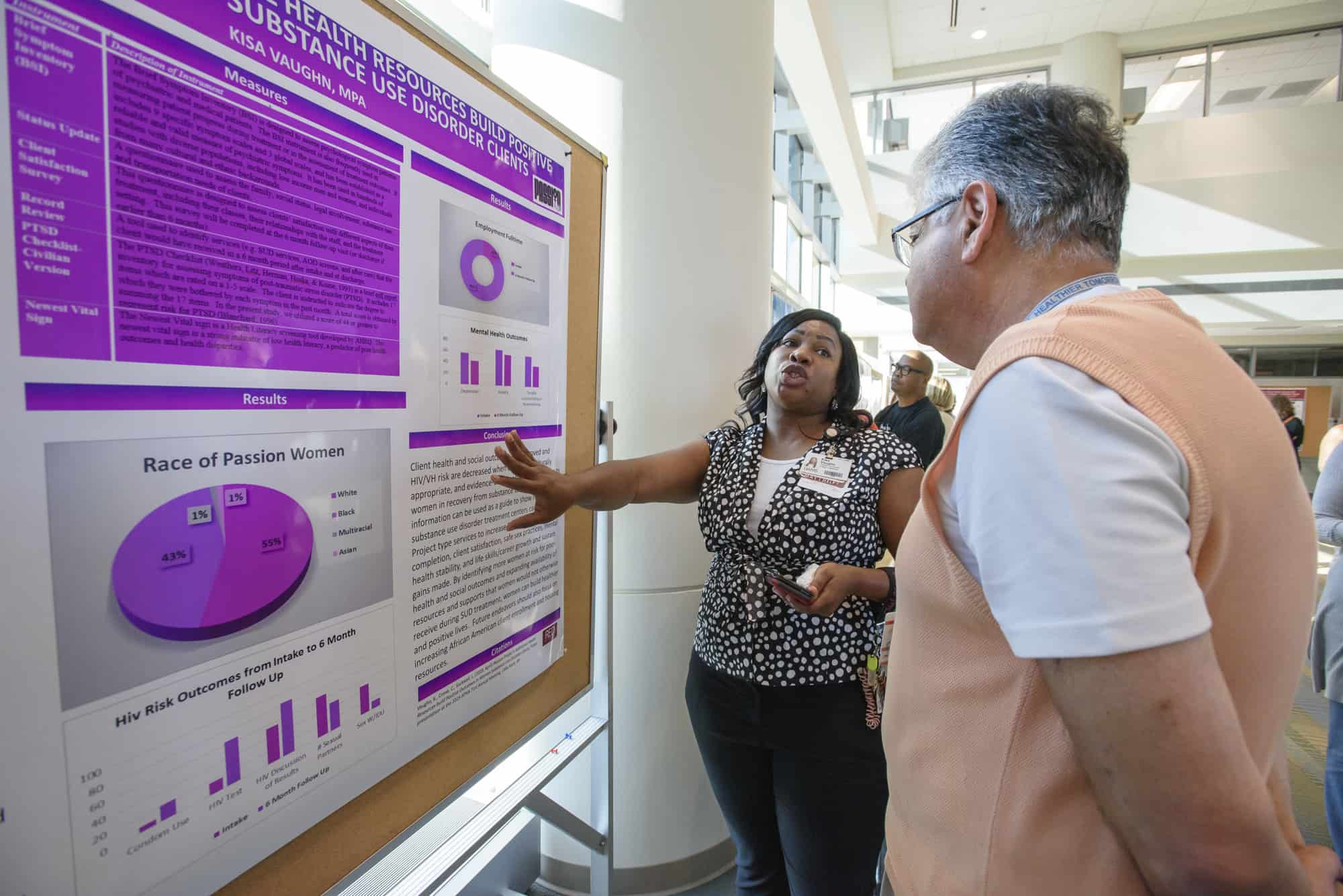 Kisa Vaughn, M.P.A., presents her poster to Reza Hakkak, Ph.D., on the Passion Project, which showed how additional health resources can improve health in African-American women with substance use disorder