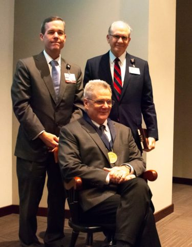 Dr. Smeltzer in commemorative chair, with UAMS Chancellor and COM Dean