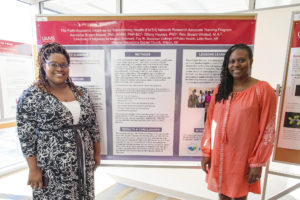 Tiffany Haynes, Ph.D., and Keneshia Bryant-Moore, Ph.D., A.P.R.N., with their poster about developing a statewide network of faith leaders as research partners.