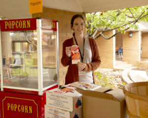 Lindsay Gilbert, an assistant professor in the Medical Laboratory Sciences program, serves popcorn during the college's fall Courtyard Carnival. Gilbert is one of 28 faculty members in the College of Health Professions who attended UAMS as a student.