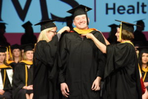 Noelle Danylchuk, M.S., and Tiffany Lepard Tassin, M.S., of the Genetic Counseling program, bestow an academic hood on graduating student Harrison Moore at the CHP Hooding Ceremony in May. Tassin, an assistant professor, attended UAMS as a student.