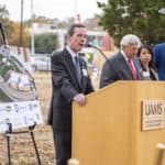 UAMS Chancellor Cam Patterson, left, speaks at the start of the groundbreaking ceremony for a $150 million energy project as UA Board of Trustees Chair John Goodson, Christina Clark, UAMS chief operating officer and Little Rock Mayor Frank Scott Jr. wait to address attendees.