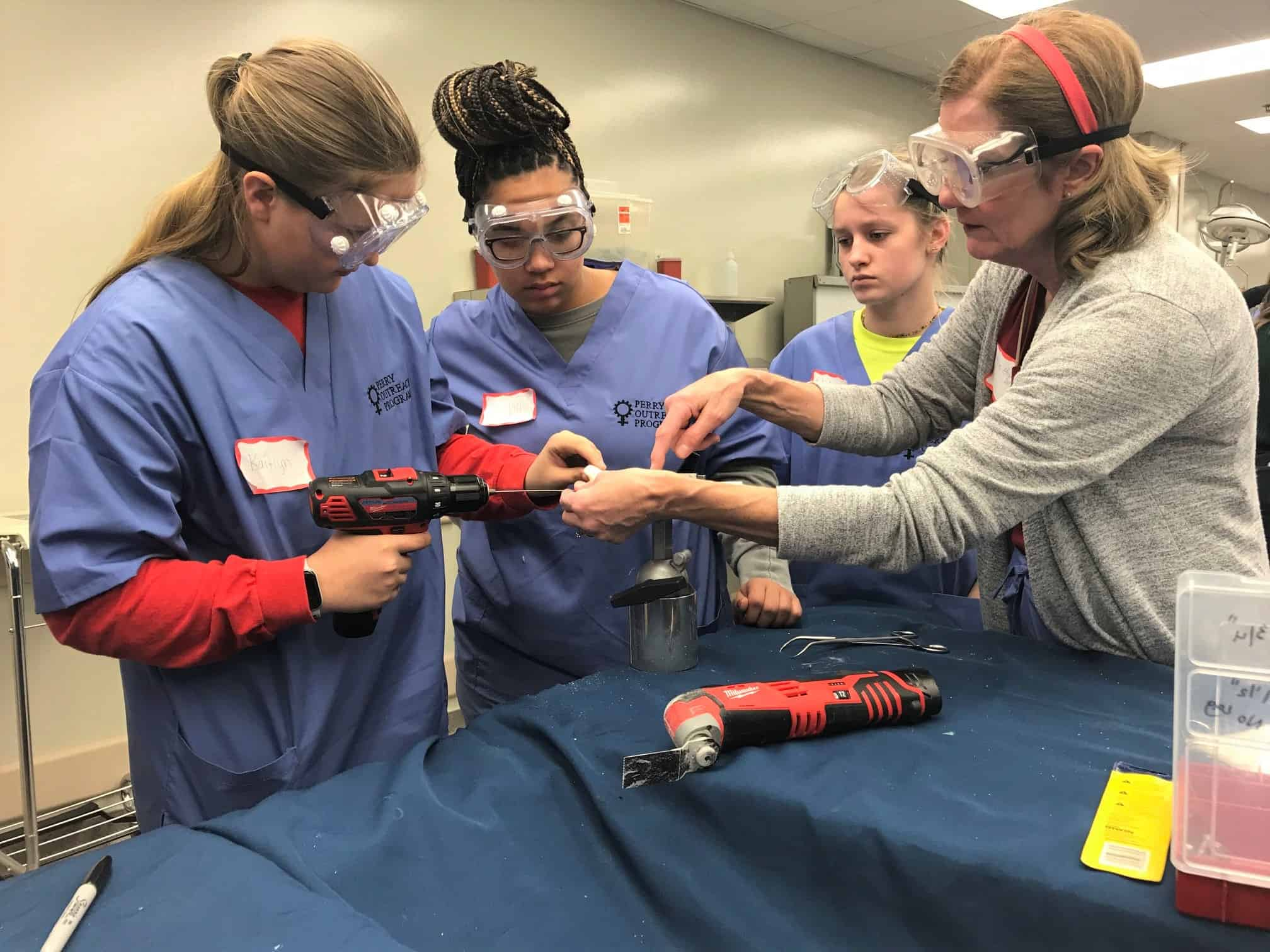 Laurie Hughes, M.D., (right) a retired orthopaedic surgeon, assists female high school students as they make repairs to simulated bones and joints.
