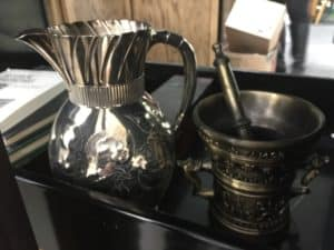 A silver pitcher that once belonged to an original founder of UAMS and an antique mortar and pestle from the College of Pharmacy await display.