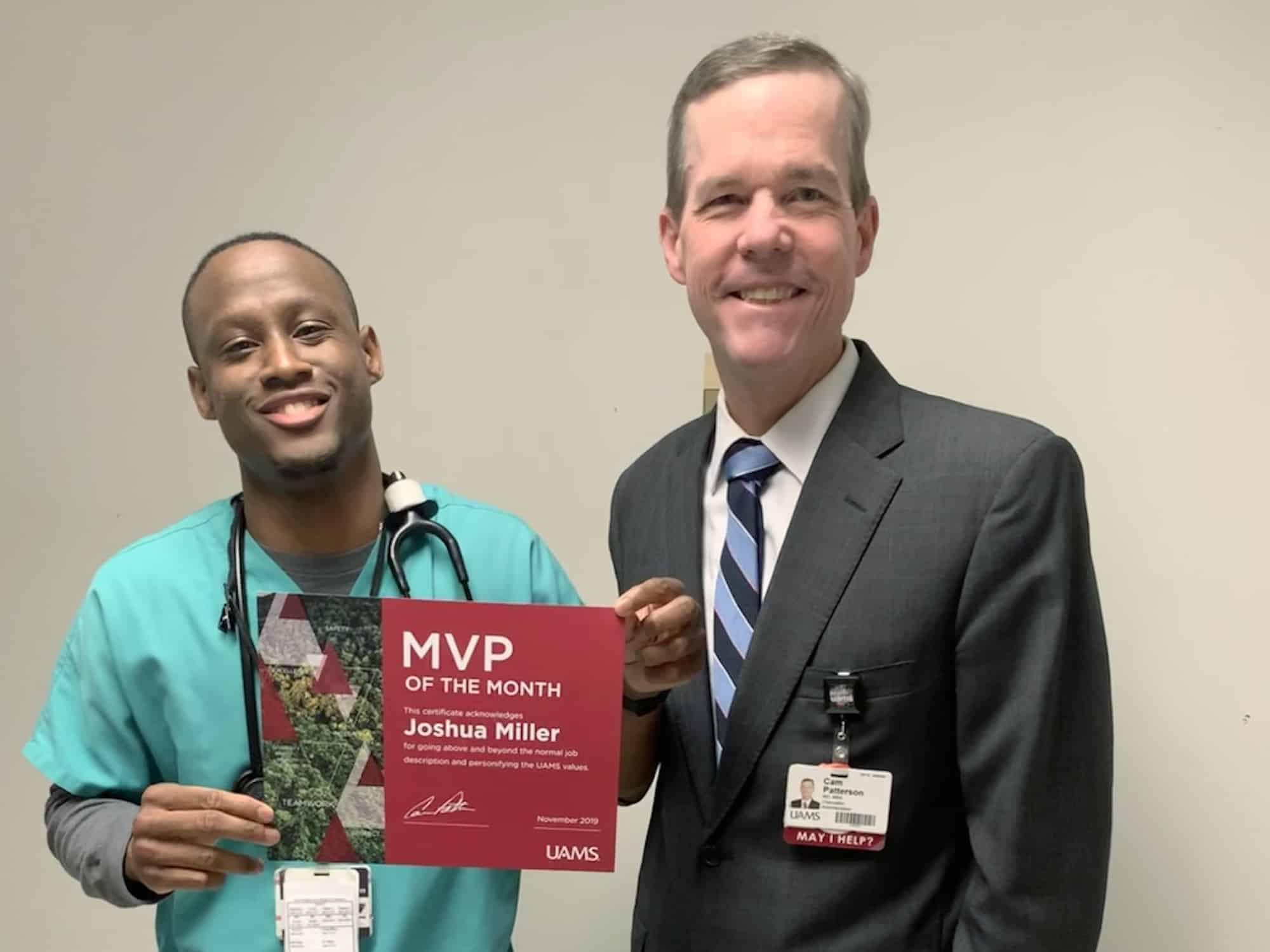 Chancellor Cam Patterson, M.D., MBA, congratulates November MVP Joshua Miller (left).