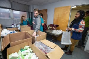 Volunteers gather donated items to create gift baskets that will be delivered to veterans.