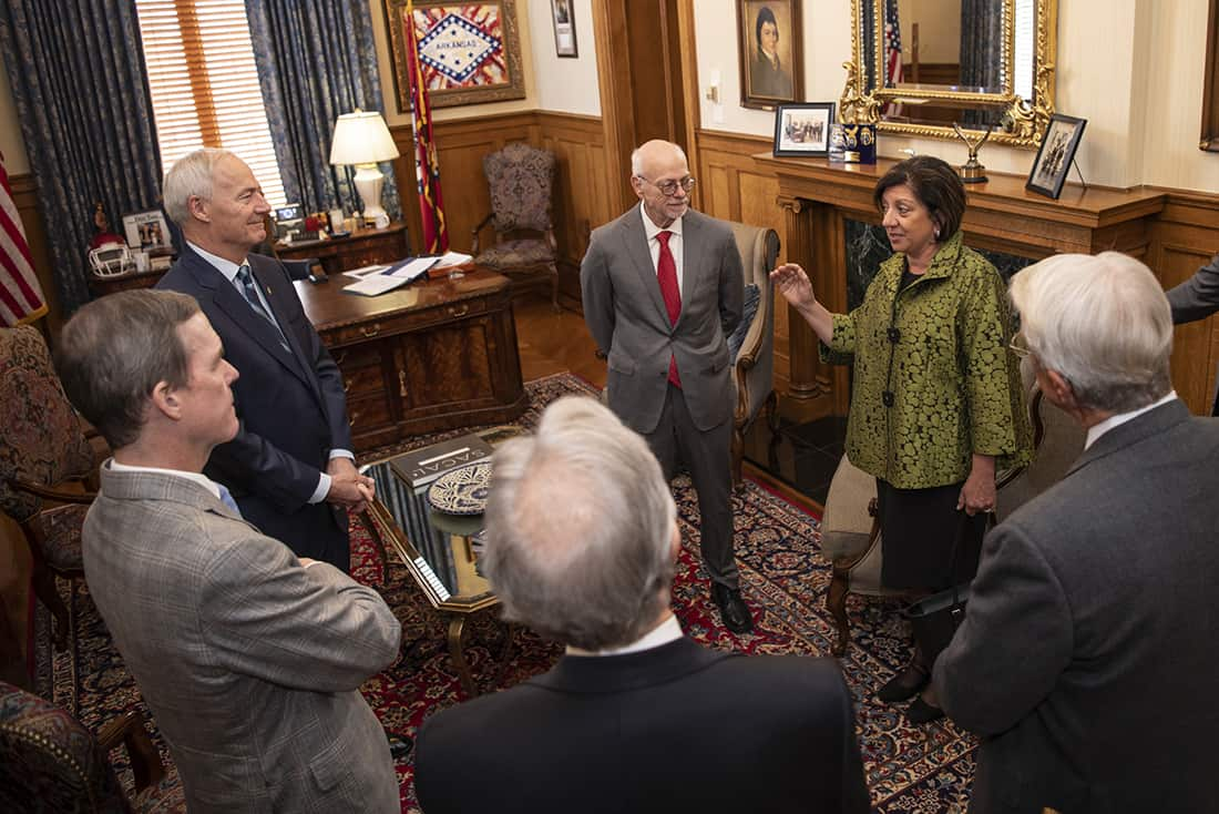 Teresita Bellido, UAMS' newest ARA Scholar, second from right, talks to UAMS Chancellor Cam Patterson, left and Gov. Asa Hutchinson, second from left and other dignitaries before the formal ceremony recognizing her as an ARA Scholar.