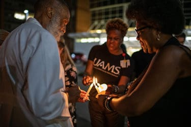 Attendees at a September vigil marking the passing of Edith Irby Jones light their candles.