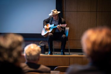 Danny Dozier, a former patient of Frazier's, plays the guitar at the investiture ceremony. Frazier performed surgery that saved Dozier's thumb many years ago.