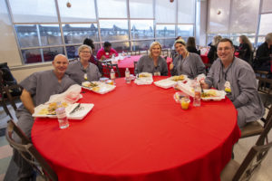 Employees enjoy their meals in the Cafeteria during the holiday party.