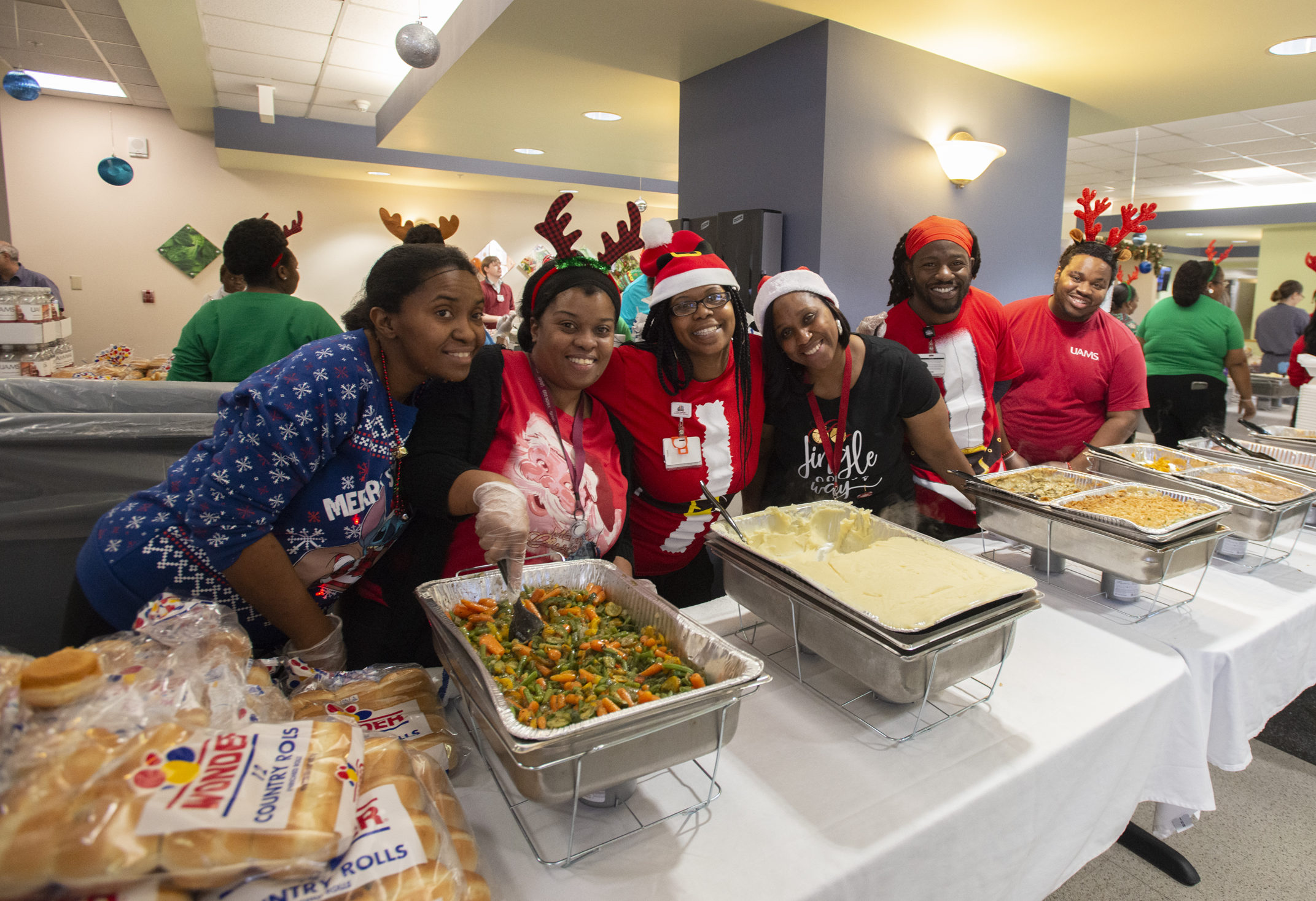"Members of the Nutrition Services team smile as they get ready to serve thousands of their fellow employees. ""Throwing a party of this size is a massive undertaking, and there is no way we could have pulled it off without Tonya Johnson and her team from Nutrition Services,"" said Annabeth Collier."