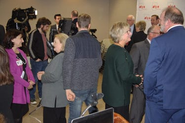 UAMS Provost Stephanie Gardner, left, and Mellie Bridewell, fourth from left, visit with media and attendees immediately after the news conference.