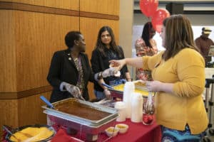 DDEI's Rosemary Nabaweesi, Dr.P.H. (at left), serves a visitor food during the lunch following the program of speakers.