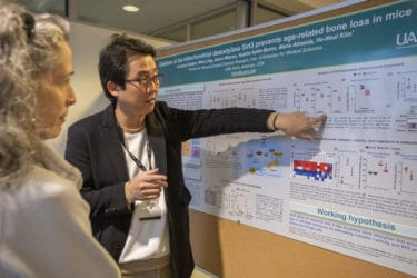 Researcher gesturing at poster