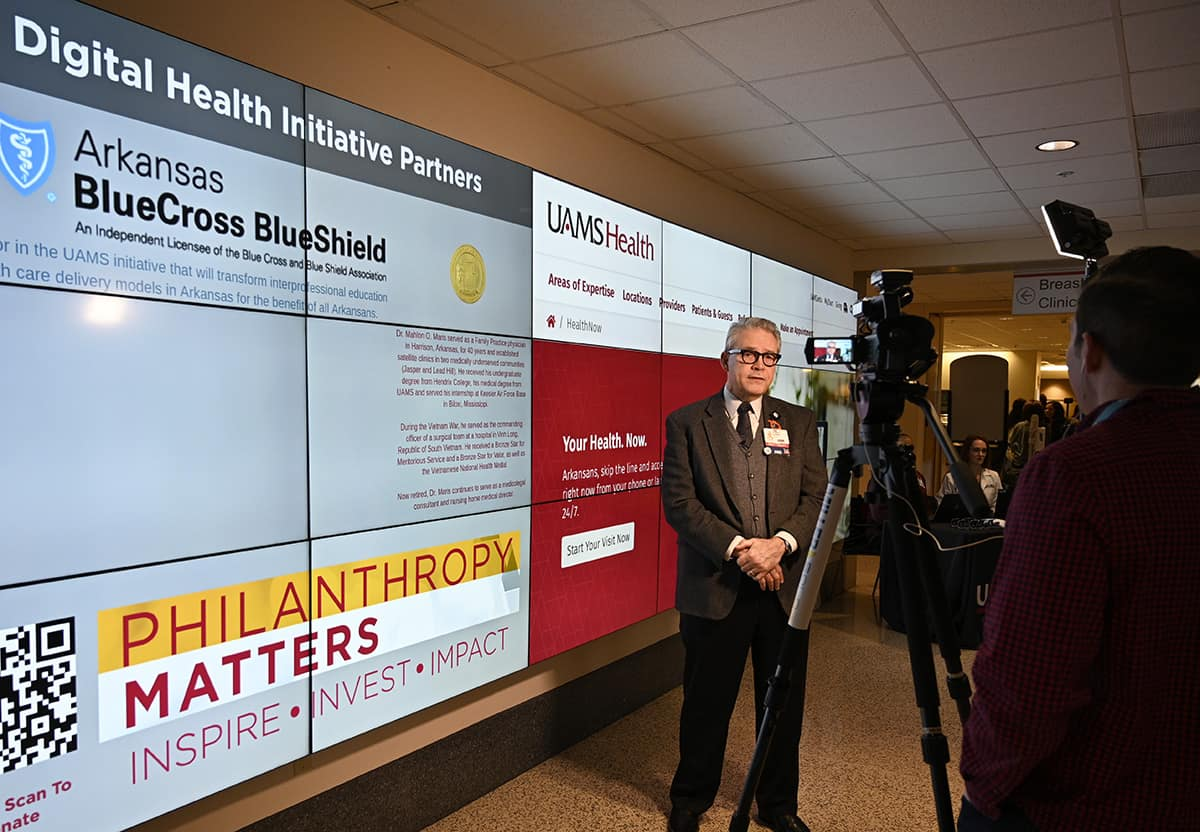 Curtis Lowery, M.D., left, answers questions during a television interview about the new UAMS HealthNow, 24-hour, online convenience health care service.