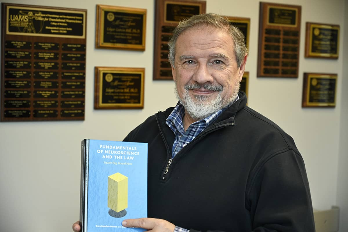 "Edgar Garcia-Rill holds a copy of the recently published ""Fundamentals of Neuroscience and the Law,"" which he co-authored with the late Erica Beecher-Monas."