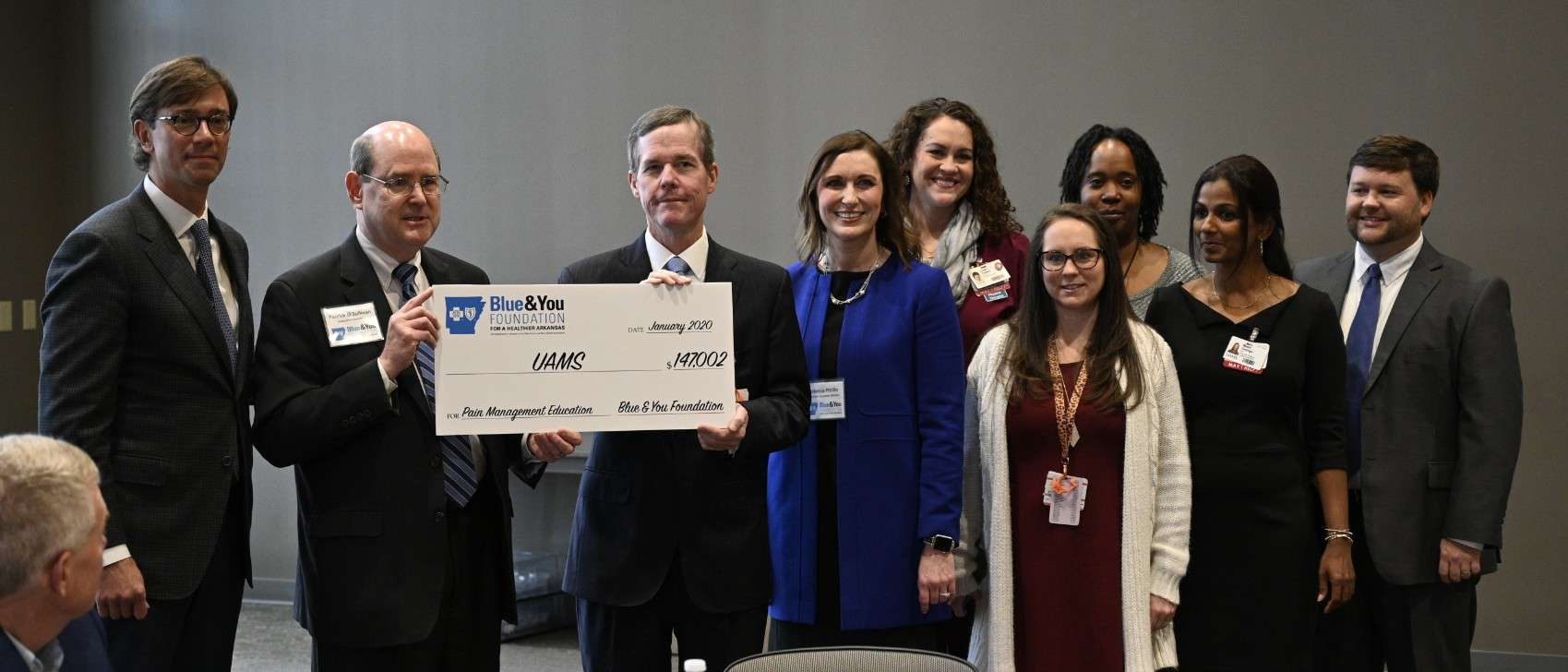 UAMS Chancellor Cam Patterson, M.D., MBA, receives the check from Patrick O'Sullivan, Blue & You Foundation executive director. Beau Blair Jr., UAMS Board of Advisors chair (at left) also accepted along with members of the AR-IMPACT team.