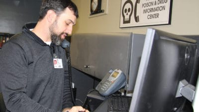 Josh Harper, Pharm.D., a certified specialist in poison information, takes a call while working in the Arkansas Poison and Drug Information Center.